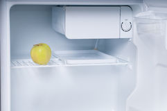 Diet. One apple in open empty refrigerator Royalty Free Stock Photos