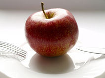 Diet. One red apple with knife and fork on white plate Stock Photo