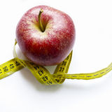 Diet. One red apple with meter tape on white background royalty free stock photos