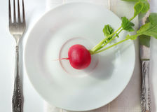 Diet. Ore red radish on white plate on white background with fork, knife and napkin; top view Royalty Free Stock Image