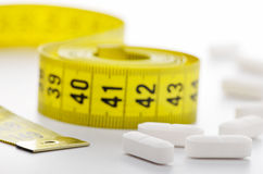 Diet pills and measuring tape royalty free stock image