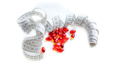 Diet pills and a tape measure Royalty Free Stock Photography