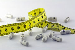 Diet pills and a tape measure Royalty Free Stock Images