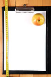 Diet plan - clipboard with measuring tape, apple Stock Photography
