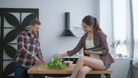 Diet plan, happy guy prepares delicious healthy salad from fresh vegetables and greens and girl sits on table with. Tablet in arms and talks in kitchen stock video footage