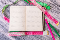 Diet plan. Healthy lifestyle concept. Nutrition journal near measuring tape and pink and green pencil on wooden background. Copy s Stock Photo