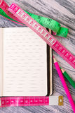 Diet plan. Healthy lifestyle concept. Nutrition journal near measuring tape and pink and green pencil on wooden background. Copy s Royalty Free Stock Photos