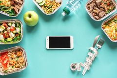 Diet Plan and Meals. Meal plan in smartphone with healthy food delivery. Fitness nutrition for diet. Daily meals in boxes on blue, top view, copy space stock photo