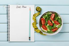 Diet plan, menu or program, tape measure, water and diet food of fresh salad on blue background, weight loss and detox concept Royalty Free Stock Photography