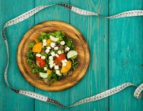 Diet plan - salad of fresh vegetables and tape measure on a whit stock image