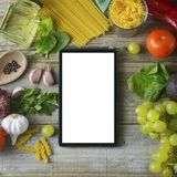 diet plannig. Set of raw food with tablet on wooden background with gadget screen with copy space. Healthy food concept, top view royalty free stock photography