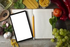 Diet plannig. Set of raw food with tablet on wooden background with gadget screen with copy space. Healthy food concept stock photography