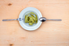 Diet. Plate with measuring tape, a knife and fork on the side. Healthy food on a wooden table Royalty Free Stock Photo