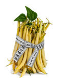 Diet portion. Portion of uncooked Yellow Wax Beans, wrapped with measure tape on white stock images