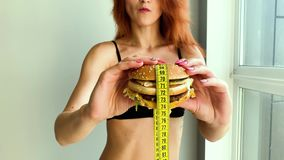 Diet. Portrait of a woman wants to eat a burger, but a glued mouth, a notion of diet, unhealthy food, a will in stock footage