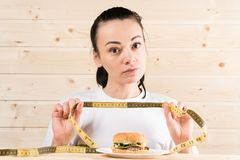 Diet. Portrait woman wants to eat a Burger but stuck skochem mouth, the concept of diet, junk food, willpower in nutrition stock image