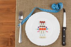 Diet products on a white plate. A plate of food supplements and cutlery. Diet food. Stock Photo
