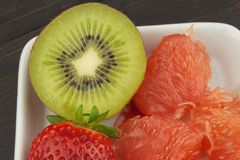Diet program, raw food. Kiwi, strawberry and red grapefruit in a porcelain dish. Royalty Free Stock Photos