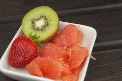 Diet program, raw food. Kiwi, strawberry and red grapefruit in a porcelain dish. Stock Photo