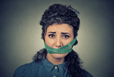 Diet restriction and stress concept. Frustrated woman with measuring tape around her mouth Royalty Free Stock Photo