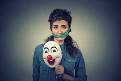 Diet restriction and stress concept. Portrait sad woman with clown mask and measuring tape around her mouth Stock Photos