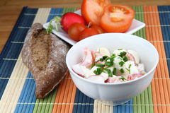 Diet salad. Salad from mozzarella, yogurt, tomato and radish in bowl. Vegetable on white plate and whole bread Royalty Free Stock Photos