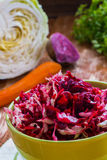 Diet salad with beetroot, carrot, cabbage, olive oil and lemon. Served in a bowl on wooden background Stock Image