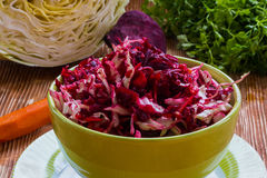 Diet salad with beetroot, carrot, cabbage, olive oil and lemon. Served in a bowl on wooden background Stock Images