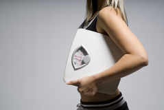 Diet scale and woman. Diet or dieting scale concept held by slim, healthy or trim woman Stock Photography