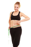 Diet. slim blonde girl with measure tape measuring waist. Diet and healthy lifestyle. slim fit smiling blonde girl young woman with green measure tape measuring Stock Images