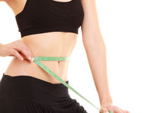 Diet. slim fit girl with measure tape measuring waist. Diet and healthy lifestyle. closeup of belly of slim fit girl young woman with green measure tape Stock Images