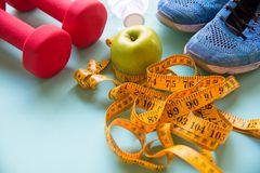 Diet slimming weight with green apple and measuring tap, scale weight on the wood plate,. Vegetables, dumbbells, colourful background.  Diet and Healthy Concept Royalty Free Stock Photo