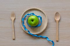 Diet slimming weight with green apple and measuring tap on the wood plate. Stock Images