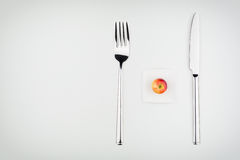 On a Diet - Small Food, Big Utensils Royalty Free Stock Images