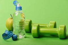 Dumbbells in green color, water bottle, measure tape and fruit. Diet and sport regime concept. Dumbbells in green color, water bottle, measure tape and fruit on stock photo