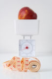 Diet start. Concept of starting a diet - measuring tape, a pair of scales with an apple Royalty Free Stock Images