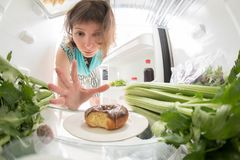 Diet struggle: A hand grabbing a donut from the open refrigerator full of greens. Diet struggle: A hand grabbing a banana from the open refrigerator full of Royalty Free Stock Images