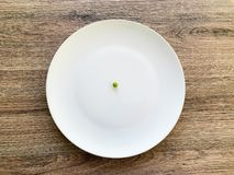 Diet. Suffering from anorexia. Cropped image pea on white plate. With fork and measuring royalty free stock photography