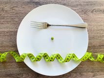 Diet. Suffering from anorexia. Cropped image pea on white plate, with fork and measuring.  stock photos