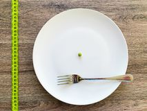 Diet. Suffering from anorexia. Cropped image pea on white plate, with fork and measuring.  royalty free stock photography
