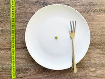 Diet. Suffering from anorexia. Cropped image pea on white plate, with fork and measuring.  stock photo