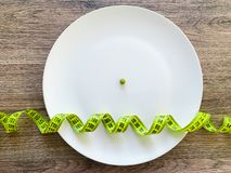 Diet. Suffering from anorexia. Cropped image pea on white plate, with fork and measuring.  stock images