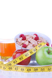 Diet tape measure apple flakes juice. Diet concept with tape measure red and organic green apple, corn healthy corn flakes with fresh raspberries and carrot Royalty Free Stock Photo