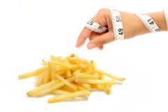 Diet temptation. Tape measure wrapped around a hand reaching for french fries Royalty Free Stock Photography