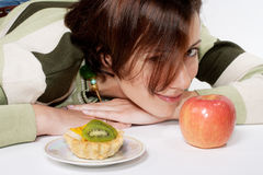 Diet  temptation - cake against apple. Smiling cute girl on diet with cake and apple Stock Photo