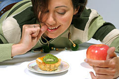 Diet  temptation - cake against apple. Smiling cute girl on diet look with pleasure at cake with fruit, apple near Stock Photo