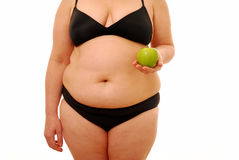 Diet time. Fat woman holding green apple standing over white background Stock Image