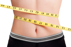 Diet Time. Woman measuring her waist with a yellow measuring tape Royalty Free Stock Photo