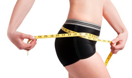 Diet Time. Woman measuring her waist with a yellow measuring tape Royalty Free Stock Photography
