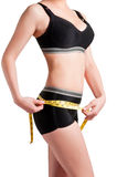 Diet Time. Woman measuring her waist with a yellow measuring tape Stock Images